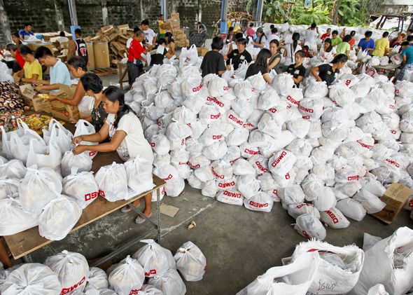 Volunteers pack relief goods inside a Department of Social Welfare and Development warehouse in Manila